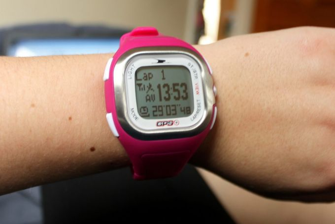 A pink gps watch on hand