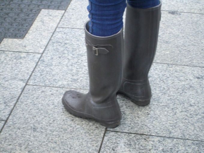 Women wearing rain boots with jeans