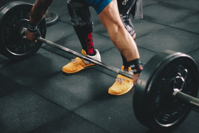 A man weaing orange crossfit shoes before lifting in the gym
