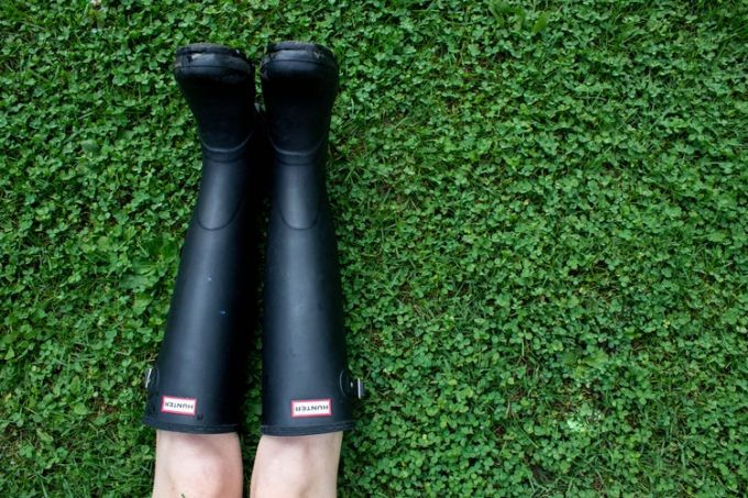 Black rain boots worn by a woman lying on the grass
