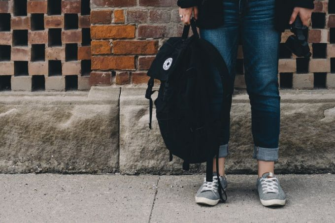A black laptop backpack held by a girl