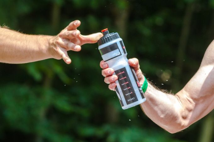 Two man passing the bottle with sports drink
