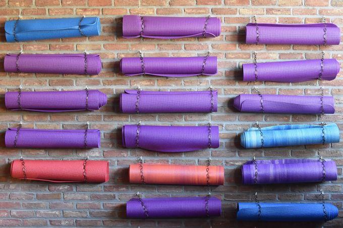 Many yoga mats hung on the wall