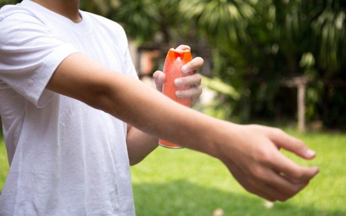 Applying mosquito spray