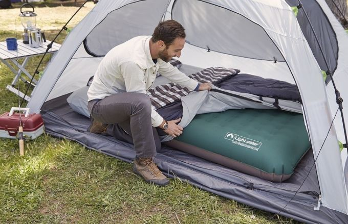 Image of a man preparing a camping bed