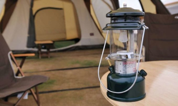 A camping lantern next to a tent