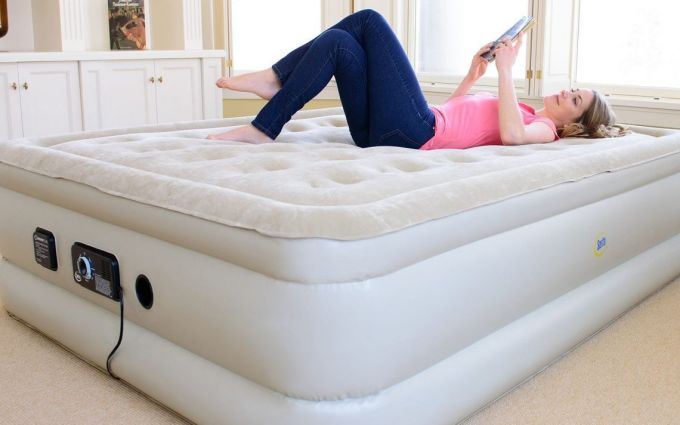 A woman sitting on a -Queen-Size-Inflated-Air-Mattress