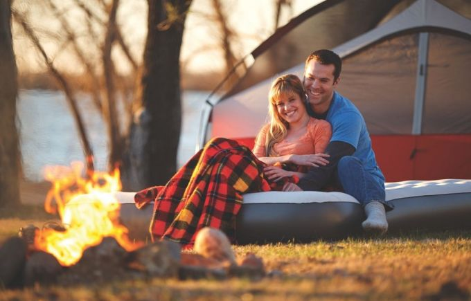 A couple relaxing outside on a camping-air-bed
