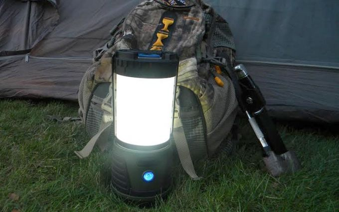 Image showing a camping lantern next to a backpack on the grass