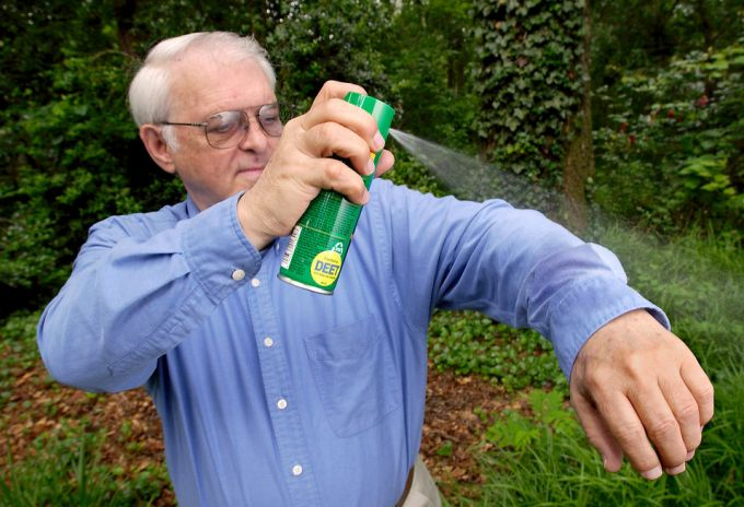 Man using insect repellent