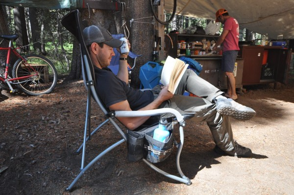 A ma sitting in a camping chair and reading a book