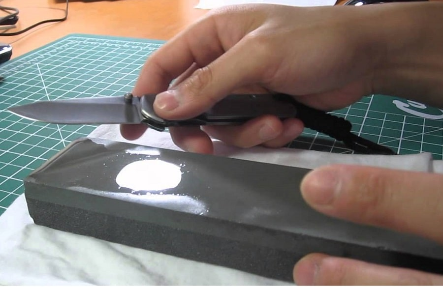 Sharpen a pocket knife with a sharpening stone