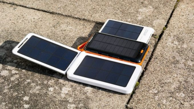 Three differernt types of solar phone chargers on the ground