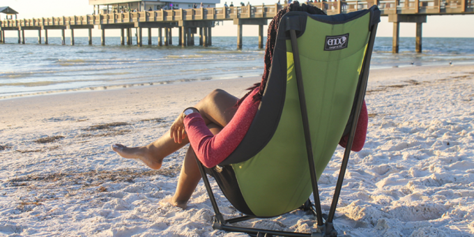 A woman relaxing in a camping chair on a beach