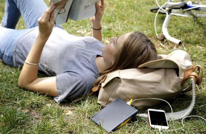 Image of a woman sitting on the grass and reading a book next to a solar phone charger
