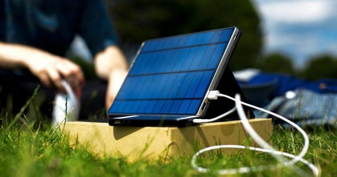Image showing a solar phone charger in the sun and a man in the background