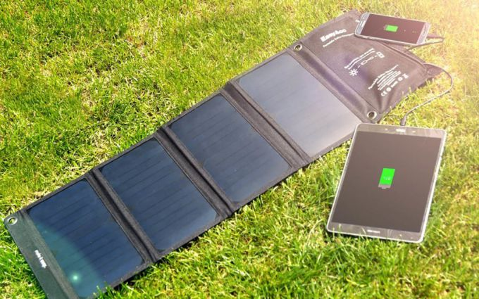 Image showing one solar phone charger on the grass and two other devices