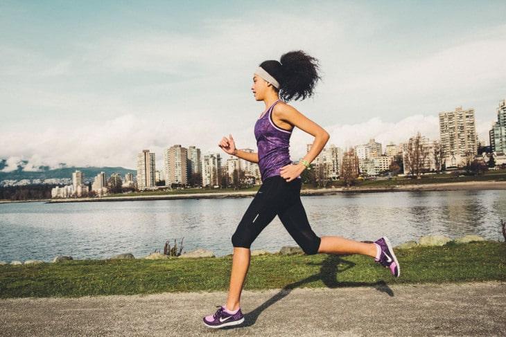 Girl running along river