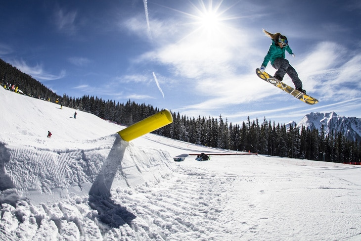 Lady snowboarder air trick