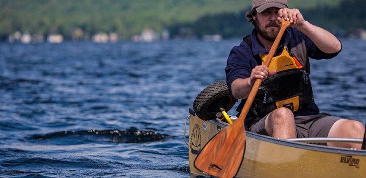 Paddling canoe on lake