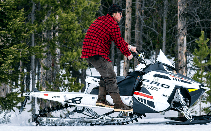 Riding snowmobile like a cowboy