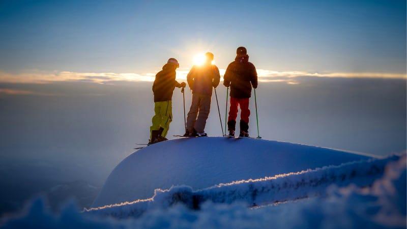 Skiers watching sunrise