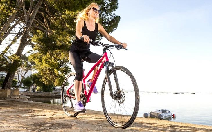 Woman biking along lake