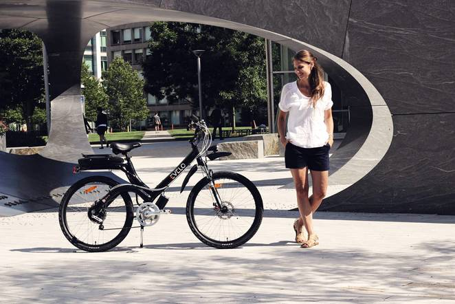 girl stands next to a bicycle