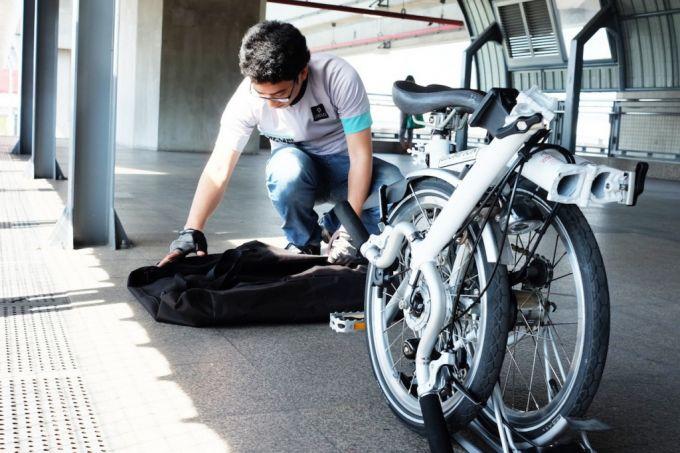 man packing folding bike