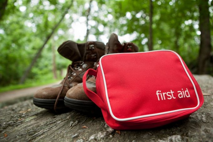 A red first aid kit with hiking boots in the woods.