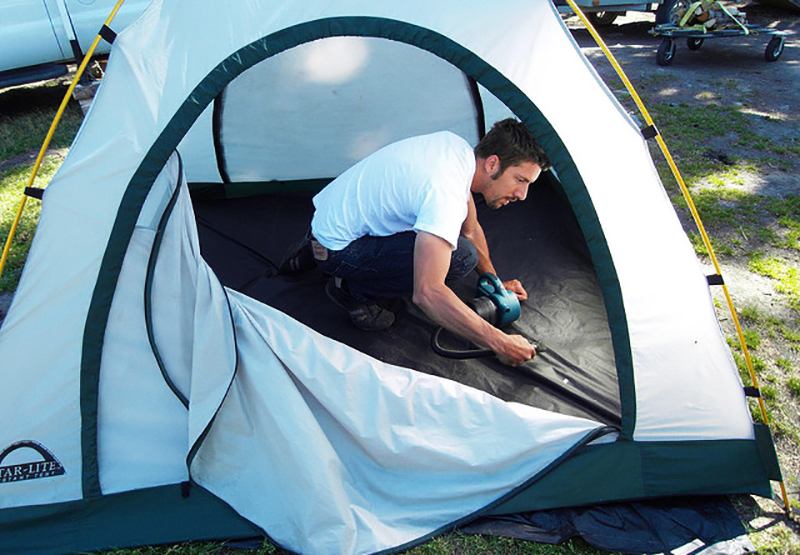 Man cleaning tent inside