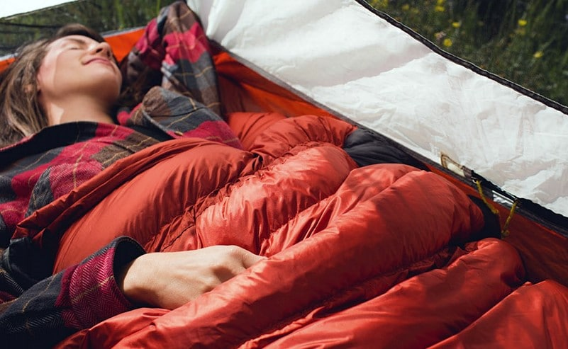woman laying in a sleeping bag in a tent