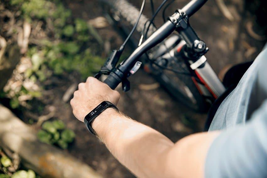 Man wearing a hand wrist fitness tracker for biking