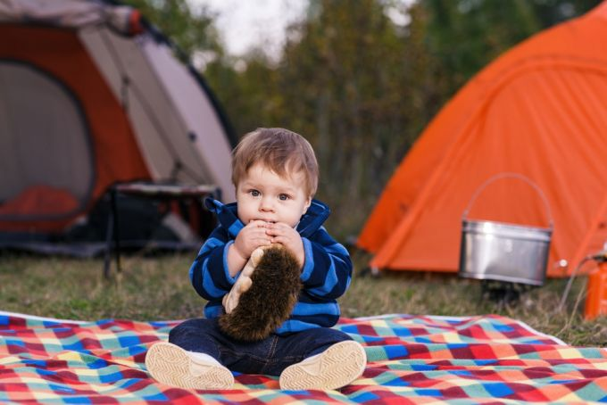 infant sitting at campsite