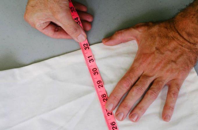 man measuring white fabric
