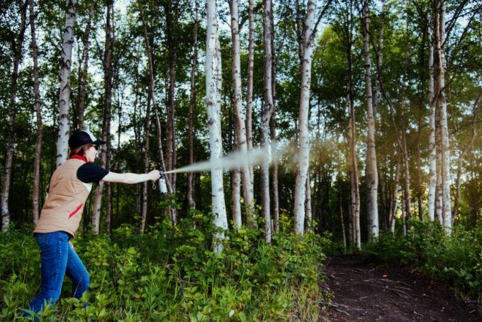 woman spraying bear spray in the woods