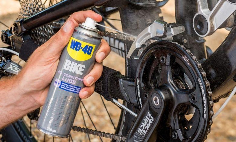 spraying on a bike chain with bike lube