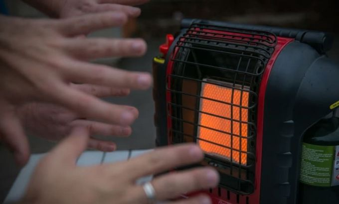 warming hands on tent heater