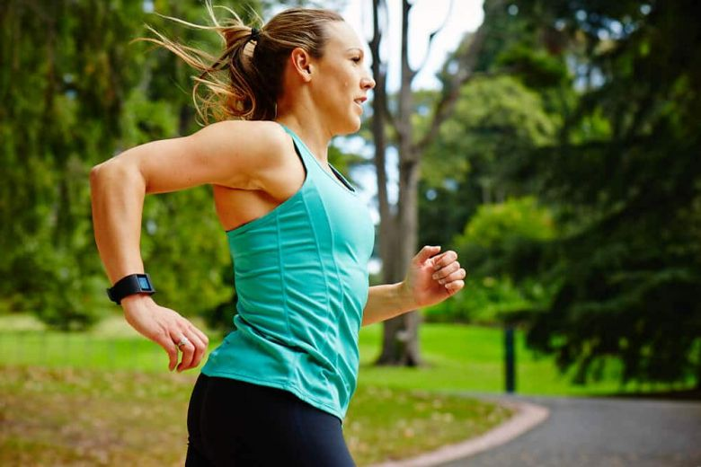 woman jogging with heart rate monitor watch