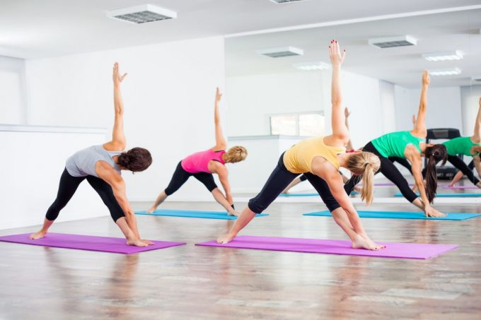Four girls practicing yoga Bikram triangle right