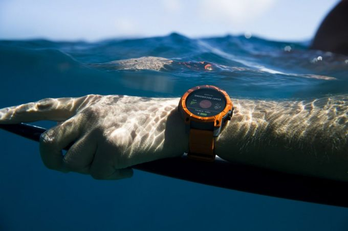A man surfing is wearing a sport watch